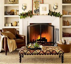 Master sitting area. Fireplace. Built in bookshelves. Bench with black legs and quilted cushion