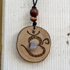 Handmade from wood, stone and hemp cord. The Om symbol is the most sacred mantra and spiritual icon in Tibetan Buddhism and Hinduism.   Approximate Measurements