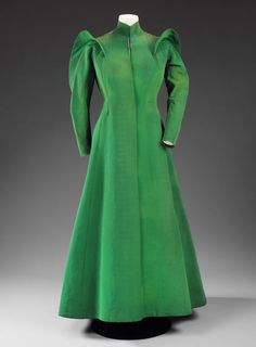 Evening coat | Charles James | Full length evening coat of bright green, heavy silk grosgrain with long sleeves of complex construction including diagonal seaming. The sleeves are emphasised by epaulettes, which run over the shoulders and down the back of the sleeves to the elbows. The jacket has a fitted bodice that flares out with an inverted kick pleat on the centre back.