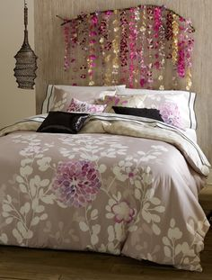 garland as 'headboard' - no tutorial, but silk flowers strung on fishing line, hung from branch