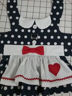 Lucy inspired navy white polka dot dress with white collar and apron trimmed in red Rick rack and applique heart. D ring for leash attachment. Cute and practical. Message me if interested in a bit bigger dog dress. Xxs fits 1 1/2 to 2 1/2 lbs., chest 8 to 10 (teacup, tiny puppy) XS