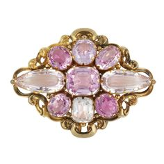 Antique Gold and Pink Topaz Brooch   The fancy-shaped brooch centering one cushion-shaped pink topaz, flanked by 2 pear-shaped pink topaz, accented by 5 oval pink topaz, altogether approximately 32.00 cts., edged by a gold scroll motif, circa 1840