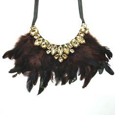 Collar estilo babero de plumas en tonos marrones y verdes con piedras color tierra y soporte en tela negra. Cierre con lazo de tela. 10,50€
