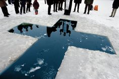 """""""Here, a Russian Orthodox priest gives his blessings before a christening in the icy waters."""" I love the reflection of the priest in the water."""
