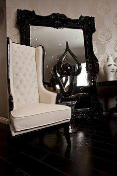 un grand miroir baroque noir, fauteuil avec dossier capitonné