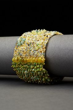 Aquamarines, turquoise, vintage glass seed beads, green garnets and 14-carat yellow gold-plated beads, hand embroidered on heavy silk with a hammered, yellow go