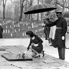 Ceremony following re-interment of the body of President John F. Kennedy to permanent grave site. Mrs. Jacqueline Kennedy places flowers on President Kennedy's grave. Arlington National Cemetery. Arlington, Virginia.