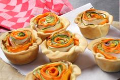 Taartjes van hartige taartdeeg met roosjes gemaakt met verschillende groentes.