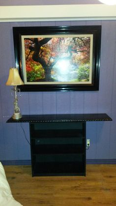 A functional DIY shelf with board & trim added to create table top. Painted high gloss black. Add a top to create balanced scale. Chairs will go on either side in front with room for baskets or even spare ottomans under extended top.