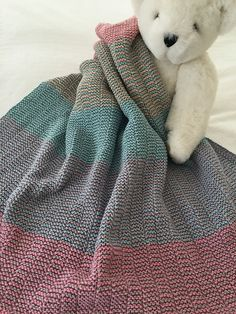 Sødt lille tæppe, der er meget let at strikke (kun ret og vrang) og kan varieres både i farvevalg og garnvalg. Her er det afdæmpede farver, men man kan også vælge klare.