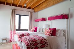bedroom is sleepover-ready with a pair of matching twin beds sporting bright pink ikat fabric.