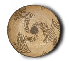 APACHE POLYCHROME COILED TRAY woven in willow, devil's claw and red yucca, with a dark medallion in the basin enclosed by whirling bands, and three triangular devices beneath the darkened rim.  diameter 18in.
