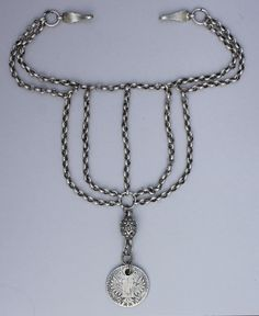 """A lovely 5-strand iznaq or chin-chain from Bethlehem. This is a large and heavy piece with strong hooks, hand made chains, a special filigree focal bead, and an old and worn Thaler. This necklace was attached to the headdress (shatweh) and worn under the chin. The classic example of the Bethlehem chin chain has seven strands and is called a """"sabe' 'rwah"""" or seven-souls necklace. This one has five souls."""