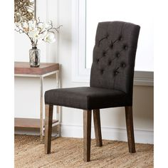 This classy chair features a deep grey linen upholstery, a tufted back and rustic natural finish. Add an elegant touch to your home with this traditional, comfortable dining chair.