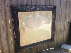 Black chippy paint wooden frame of an old 25th edition map