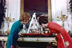 Pat Nixon and Julie Eisenhower give the press corps members a tour of the White House Christmas decorations Dec 13, 1971