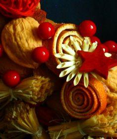 Vítací věnec 8 Ozdobný věnec z tónovaných přírodních materiálů s náznakem přicházejících vánoc. Je vyroben ze skořápek oříšků, pecek, trávy, slámy, sušených pomerančů, pomerančové kůry, šustí, lýka a přízdob. Upevněn je na pevném slaměném korpusu. Korpus je obalen přírodním papírem. Ze zadní strany je poutko na zavěšení. Na dveře se dá pověsit ...