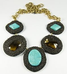 Imelda - Turquoise -  The perfect blend of edgy and glamorous, this statement necklace consists of taupe colored rhinestones and turquoise colored magnesite surrounded by gunmetal colored chain. To bring balance to this edgy look, neck chain consists of a feminine large gold toned chain with lobster claw clasp closure.