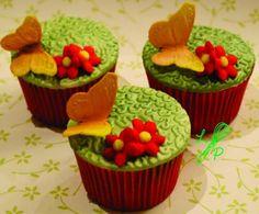 Cupcake com decoração de borboleta e rosa, ideal para festa infantil.