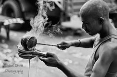Men at Work.   This photograph shows a local man filtering the tea through four filter pans. This is completely normal as many tea-stalls use cloth filter instead of steel filter