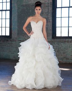 Justin Alexander signature wedding dresses style 9821 The intricately hand beaded crystal and pearl sweetheart bodice, dropped waistline and full organza ruffle skirt will make a bride look and feel fierce on her wedding day.