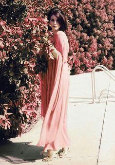 Lana Del Rey outdoor photoshoot long pink dress next to matching pink flora