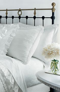 A charming guest bedroom with ruffle, lace and eyelet bedding, alongside freshly-picked peonies