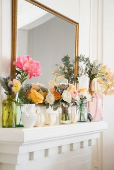 Multiple Vases with Flowers on a Mantle