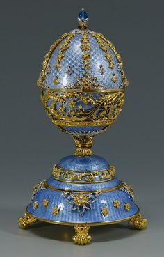 """Franklin Mint House of Faberge egg music box, """"The Peter Carl Faberge 150 Anniversary Imperial Egg Fountain of Jewels"""". Crafted of sterling silver with 24KT gold accents, white sapphires and blue guilloche. The top opens to reveal a fountain with clear and blue crystal drops and the waltz """"The Blue Danube"""" plays. Original paperwork included. 6 3/4"""" H."""