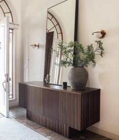 Mid century modern vibes with this console table and sconces.   #LightingDesign #lighting #midcenturymodern #sconces #hallway #entryway #frondoor #largemirror #homedecor #onlineshopping #interiordesign