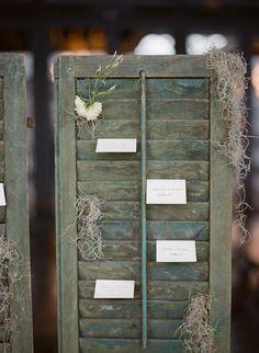 display escort cards on an antique shutter, photo by Kate Ignatowski http://ruffledblog.com/new-orleans-inspired-wedding-ideas #seatingchart #escortcards