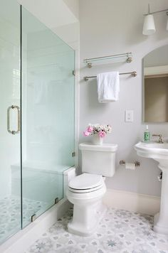 A white pedestal sink sits on gray and blue mosaic floor tiles beneath an arched vanity mirror mounted on a light gray wall beside a vintage glass shelf fixed above a polished nickel towel bar located above a toilet.