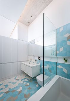 Modern bathroom with tumbling blocks geometric tile pattern in blues, white, and grey on walls and floor // Doehler+/+SABO+project