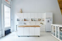 The wheels on the bottom of this movable white kitchen island with a wood countertop, lets people move it around so they can prep things closer to the rest of the counter or move it out of the way entirely when they need more floor space.
