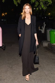 Karlie Kloss in a minimal black slip dress with a long blazer and strappy sandals