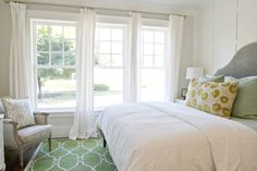 Caitlin Creer Interiors Tiek Built Homes - Fresh spring bedroom design with Surya fallon green rug, West Elm gray Scroll Headboard, Thibaut blue & green suzani fabric pillows, gray vintage Bergere chair and decorative wall panels.