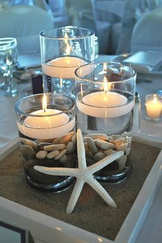 Nautical centerpieces floating candles with pebbles? Maybe with a toy sub in the water?