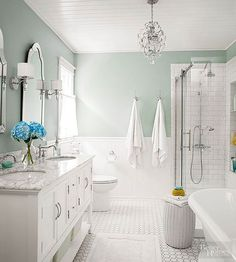White floors, countertops, and finishes go a long way toward creating breezy spick-and-span spaces. But all-white spaces can come across as cold and sterile. Be sure to introduce materials with dissimilar textures, fun furnishings, and a rich wall color, like the subdued green-blue blend pictured here, to build interest and warmth into your bathroom design.