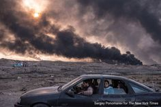A family flees the fighting in Mosul, Iraq's second-largest city, as oil fields burned in Qayyara, Iraq, on November 12, 2016. In its sixth week, the military campaign to retake Mosul from the Islamic State had bogged down in a grueling fight. Seeking to escape the bloodshed, more civilians than ever took the risk of evacuation, hoping to find help if they could make it past the militants' gun range.