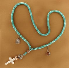 """Necklace with turquoise beads and white bronze charms. Overall length is 19 1/2"""", $309."""