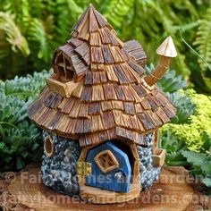 This fairy house has a shingled roof, blue hinged door, and a crooked smoke stack.