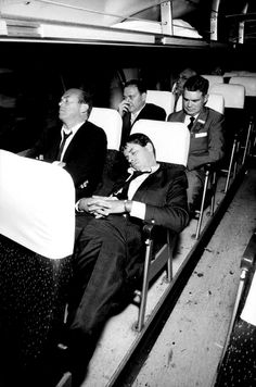 Jerry Lewis sleeps with unidentified members of his entourage on bus en route to Far Rockaway, New York, July 13, 1961