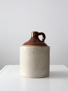 circa 1910s This is an antique stoneware two gallon jug. The heavy stoneware jug features a brown albany slip. It is unmarked. - 2 Gallon unmarked - natural glazed stoneware with brown Albany slip (gl