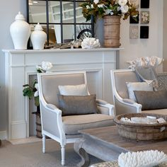 Linen chairs with grey cushions in front of mantle.