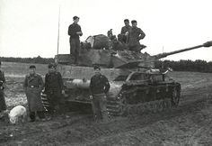 This Panzer 4 Ausf H crew is standing around while repairs are being made to the engine