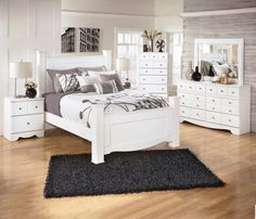 Stylish white bedroom set with wide 4-post bed. Kimbrell's Furniture.