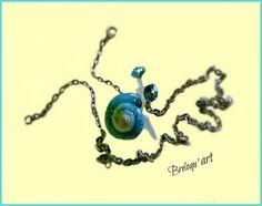 Pendentif escargot avec une véritable coquille, vernie en bleu pailleté et 2 strass cristal swarovski bleus(très lumineux), en guise d'yeux. Vendu avec une chaine en métal argenté, maille forçat.  Exemplaire original et unique.  la Coquille a été solidifiée, grâce à l'injection d'une résine; celle-ci a également permis à reconstituer le corps du gastéropode!  Les strass (yeux) sont liés à leur corne respective grâce à un vernis-résine solidifiant qui recouvre l'ensemble du pendentif!