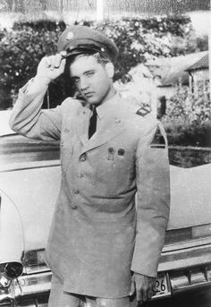 """Photo caption in the Memphis Press-Scimitar, Tuesday, June 3,1958: """"ONLY A PEEK--Pvt. Elvis Presley lifts his garrison cap an inch or two for newsmen, but no more. 'It's in the ugly growing-out stage,' he said, about his hair."""" Press-Scimitar Staff Photo by William Leaptrott. Elvis was on a two-week leave after he had completed basic training at Fort Hood, TX. This photo was taken at Graceland on June 2, 1958."""
