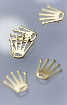 Rolex crown appliques in 18ct yellow gold awaiting placement on the dial of Rolex Lady-Datejust 28 watches. The Rolex crown was first registered in 1931 and remains the symbol par excellence of the brand to this day.
