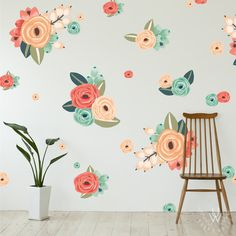 An assortment of small and large floral wall stickers spaced in a pattern on a grey wall behind a chair and small plant. The larger floral clusters feature a light pink stem, and one to three coral flowers in orange, red, and green. Each flower features a high level of detail and a variety of shades to give a real life-like appearance.